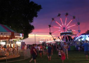 Photo of the Fair's carnival at night, with the ferris wheel in foreground..