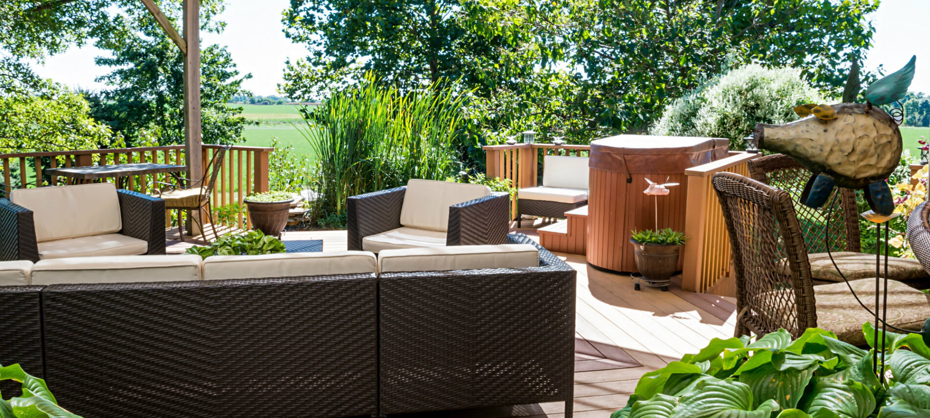 Deck with outside furniture, plants and a view of farmland.
