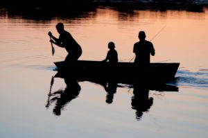 Three fishermen in a small boat on a quiet lake at sunset