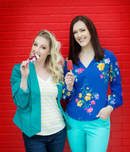 two women holding and eating popsicles
