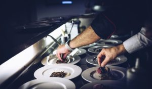 two hands plating food