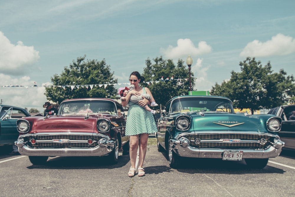 woman holding a baby in front of two vintage cars