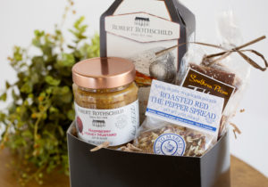 A gift basket with a jar of honey mustard, pecans, and two dip packages.