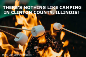 A photo of marshmallows on sticks roasting over a campground fire.