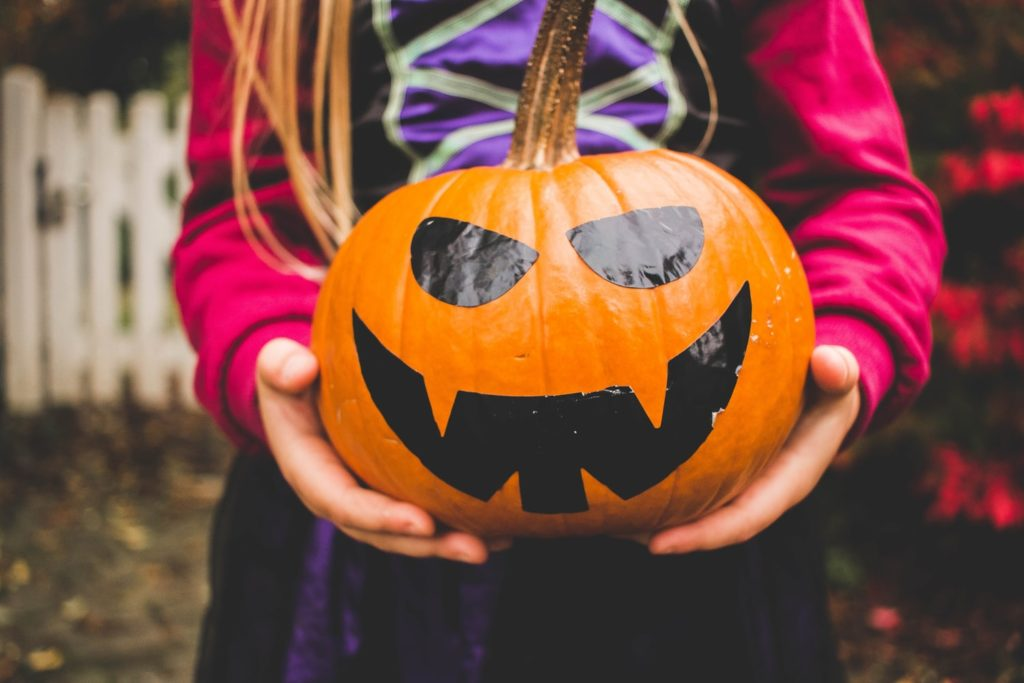 Small hands holding an orange jack o lantern with black eyes and mouth