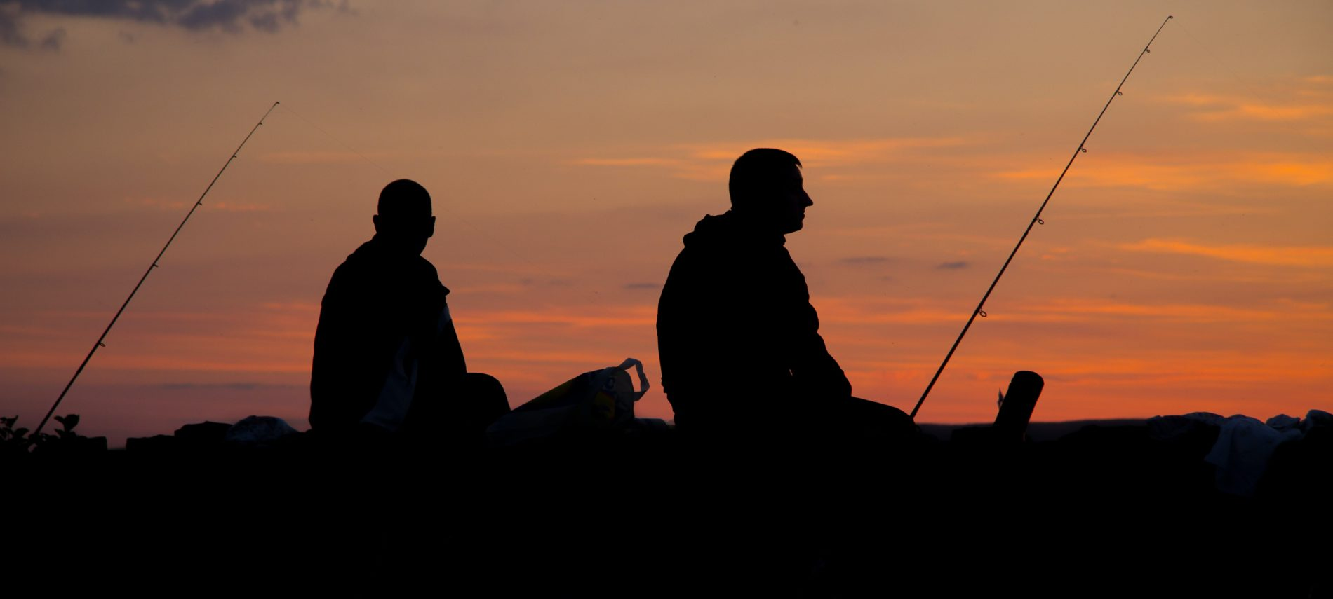 Two fishermen in silhouette at dusk