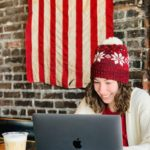 Woman wearing a red stocking hat working at her computer. Behind her is a brick wall with an American flag hanging down it.