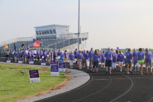 The high school track lined with participants wearing purple t-shirts.