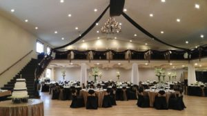 Banquet room decorated with white flower and velvet streamers and chair covers, Balcony with carpeted stairs, round table with four-tier cake, wood floor.