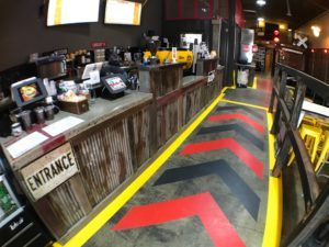 A look down a long counter at the shop showing bright red, black and yellow arrows on the floor.