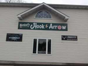 Tan sided multi-story building with Black Sign: Henkel's Hook & Arrow, sign for Diamond Archery and Hoyt Retailer.