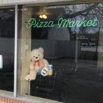 Teddy Bear Mascot for Pizza Market holding sanitizing products
