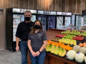 Owners standing in front of bins of fresh fruits and vegetables in new store