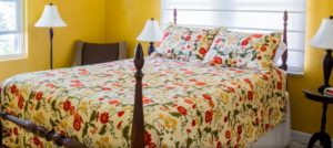 A four-posted bed with a red and cream floral comforter in one of the guest rooms at Timmermann House.