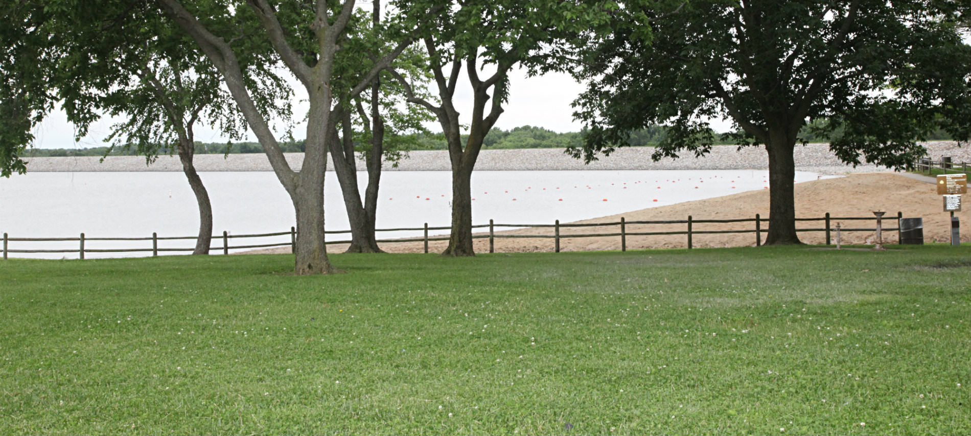 Lake with sandy beach with treens and wooden fence. grassy area in front.