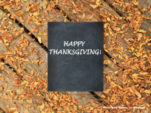 """A chalkboard that says """"happy thanksgiving"""" lying on a picnic table scattered with leaves"""
