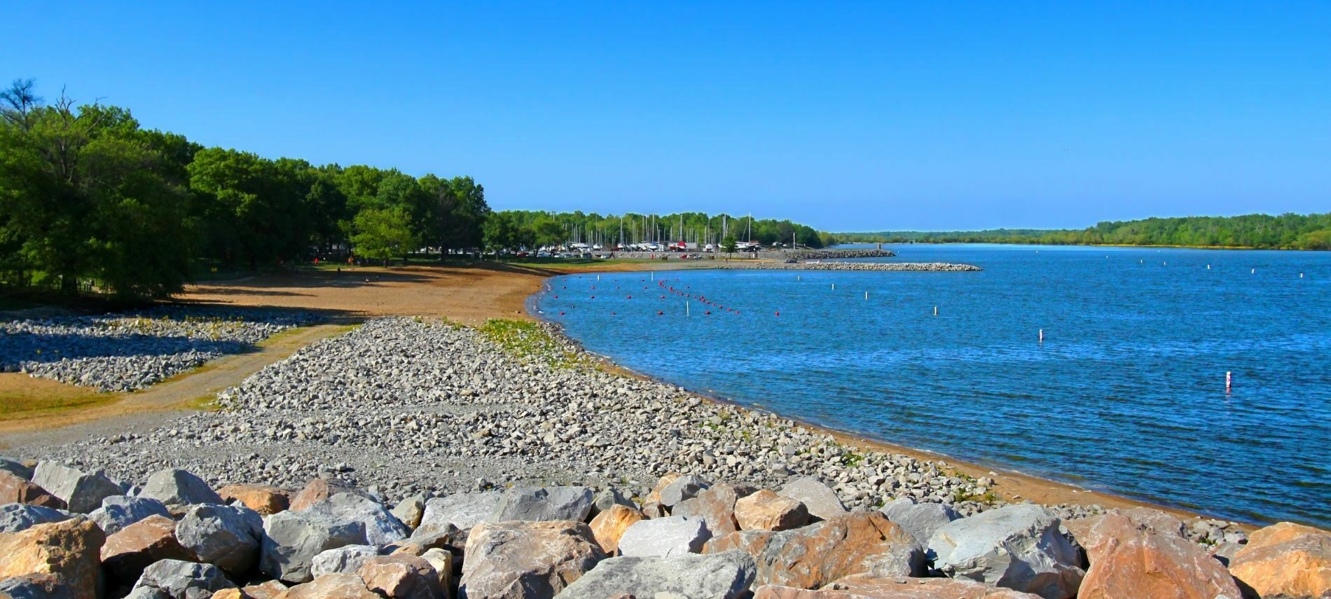 Beautiful view of Lake Carlyle with rocky shore and sailboats in the distance