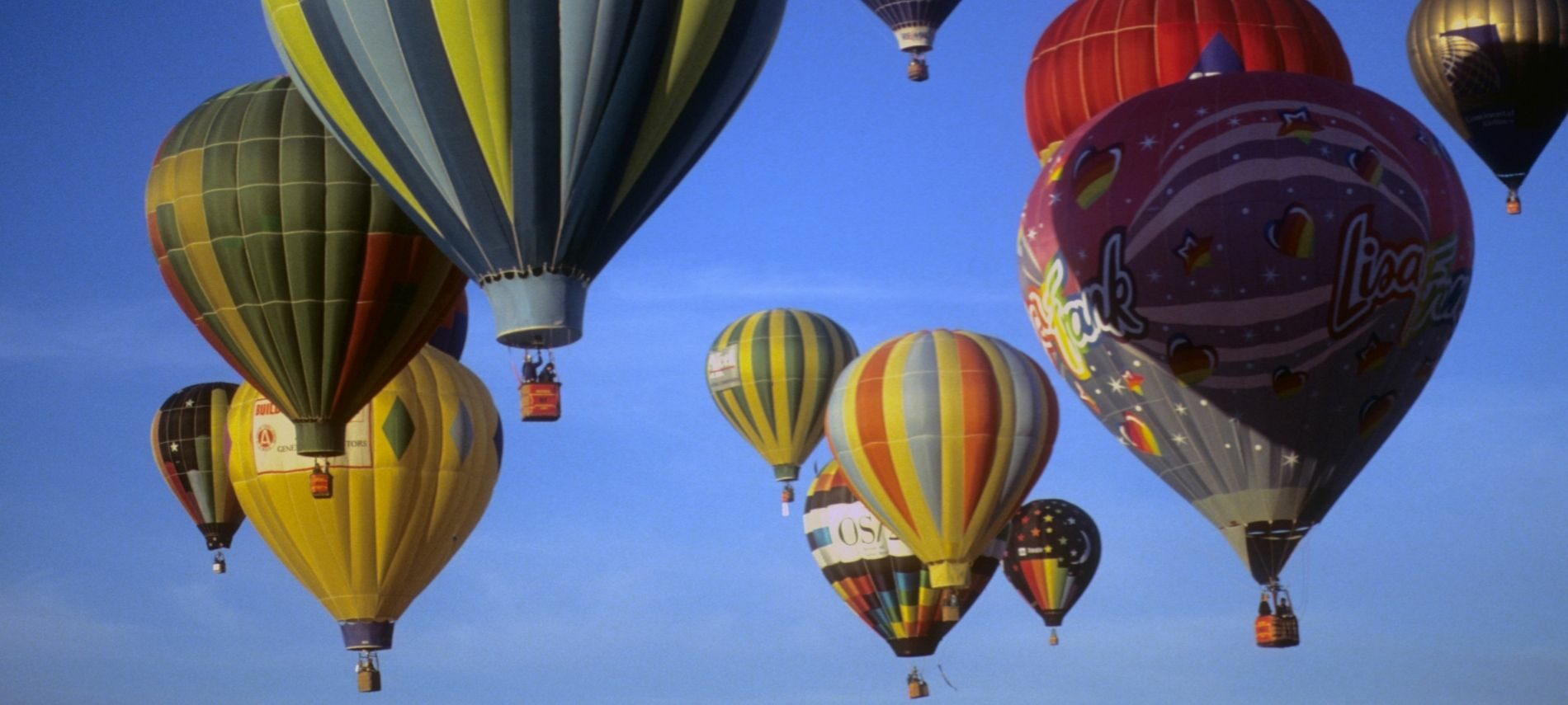 Many bright colored hot air balloons in a deep blue sky