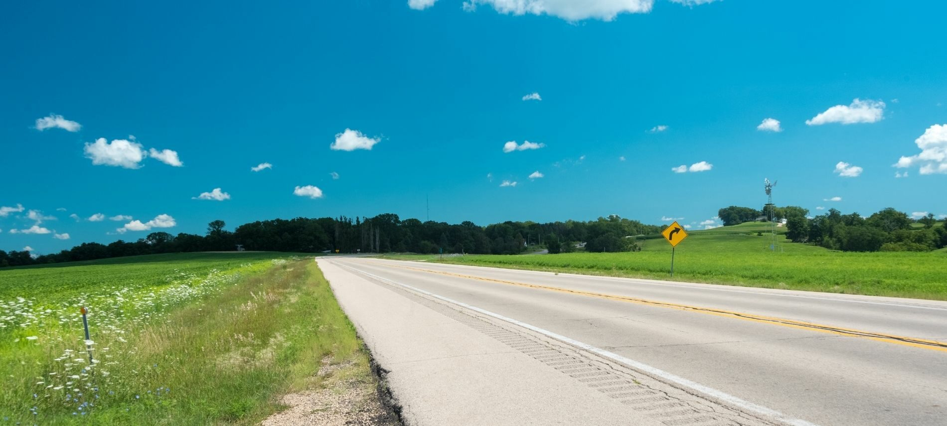 Country road in Clinton County surrounded by blue skies and country views.