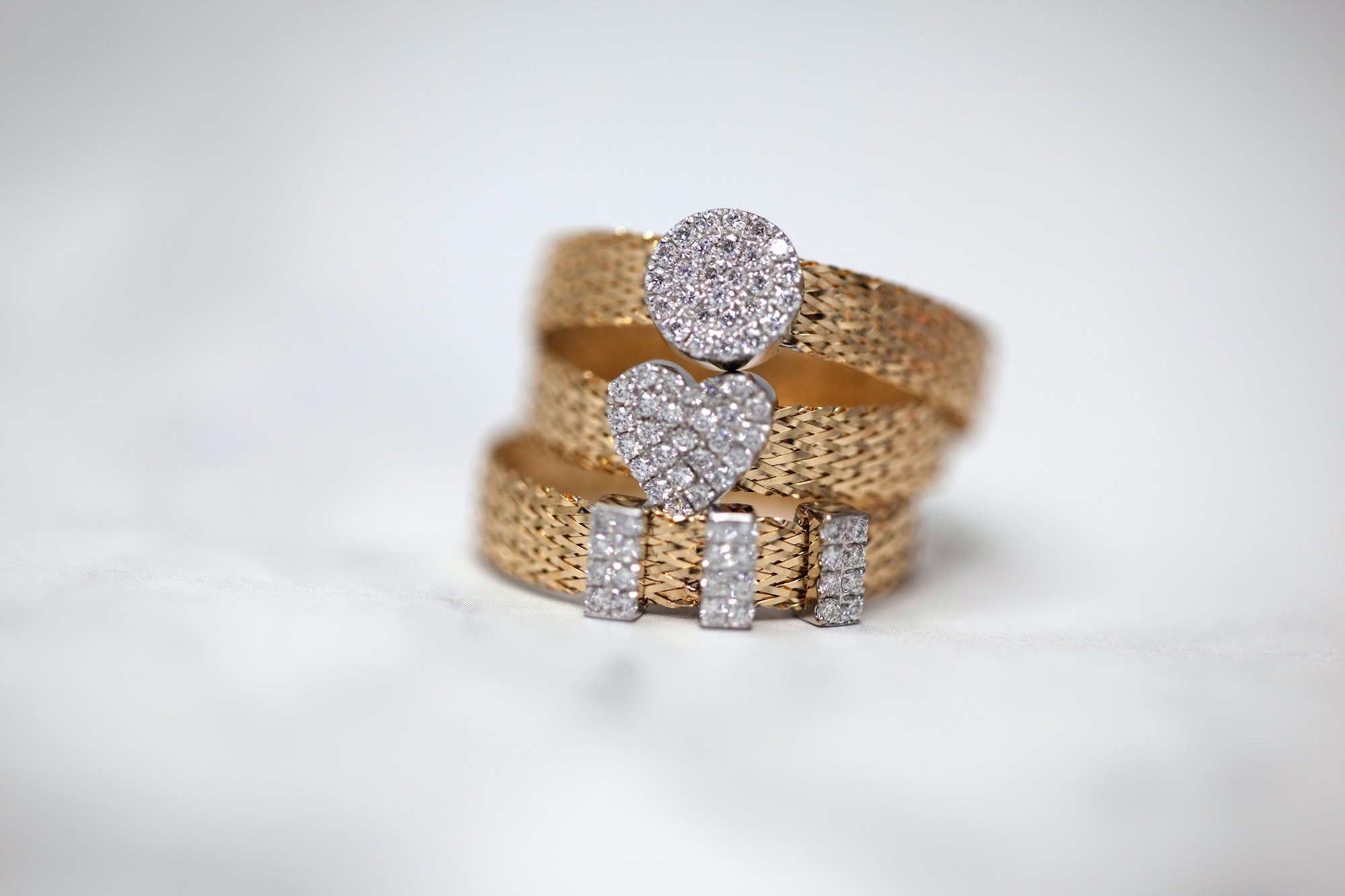 Three stacked gold rings with diamonds