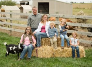 The family of six sitting on hay bales.