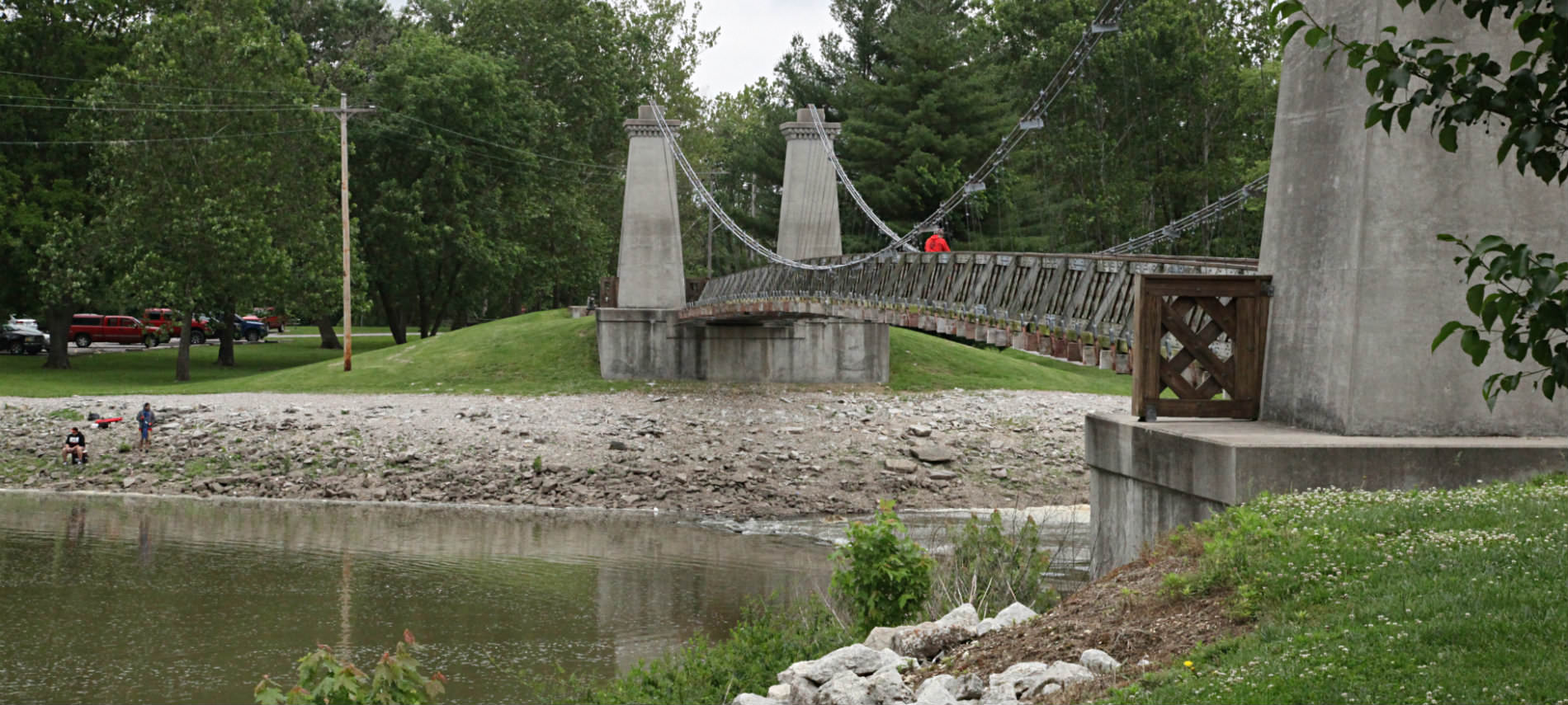 Bridge with pillars over creek, biker with red jacket on bridge, fishermen on bank of creek, parking lot in park.