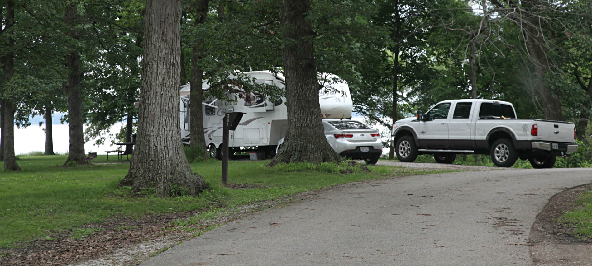 Fifth wheel white camper in woods with huge trees, white pickup and car parked in area, lake in distance.
