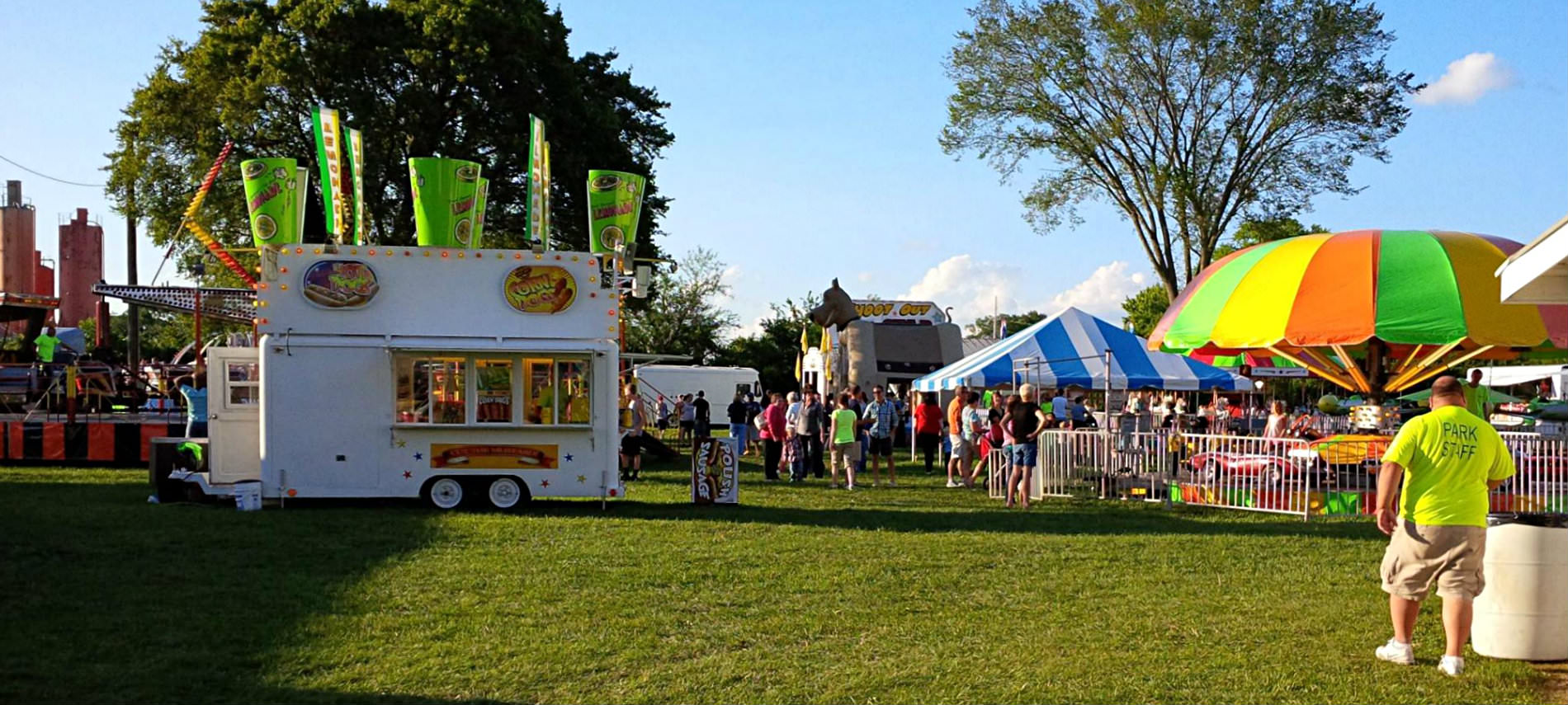 Concession Stand Trailers on green grass at Carnival with spectators, covered rides with trees in background.