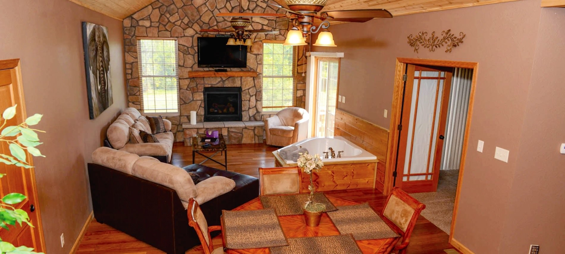 Large room with stone fireplace, flatscreen television, ceiling fan with lights, couch, triangle tub, Wood table & chairs.