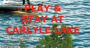 """Man standing on front of boat on lake water with text, """"Play & Stay at Carlyle Lake."""""""