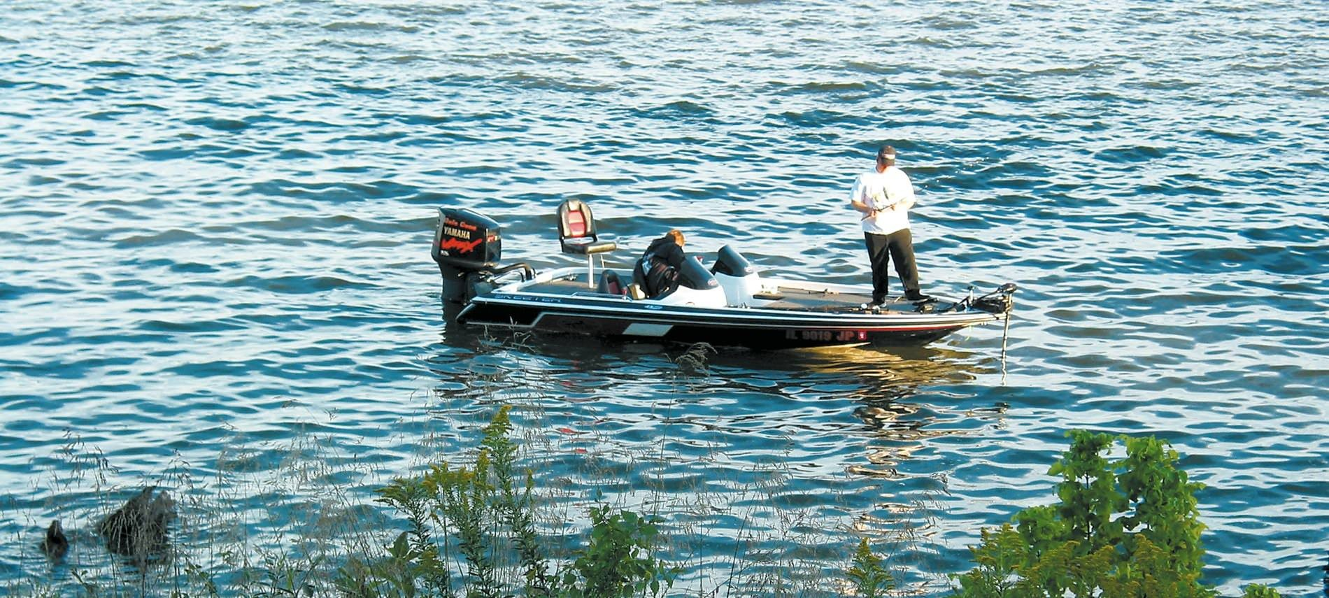 Man with white shirt and jeans standing on motor boat on choppy ocean waters getting ready to fish.