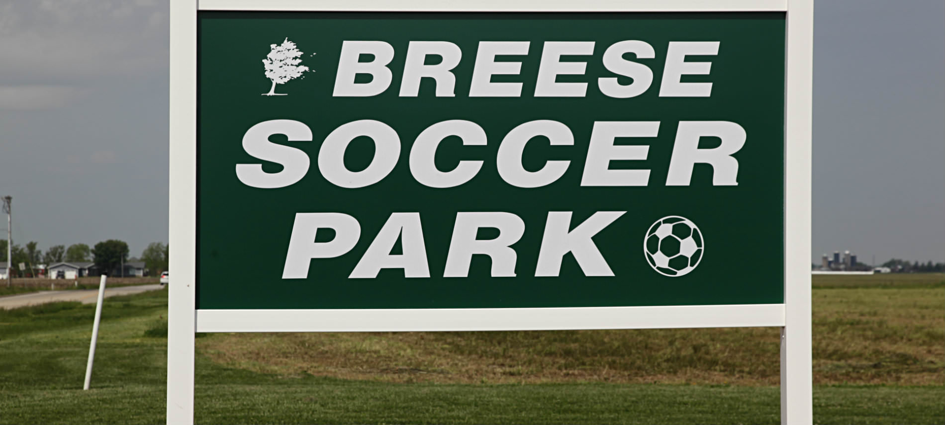 Green wood sign with white border and lettering for Breese Soccer Park, along a dirt raod, house and trees in background.
