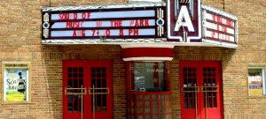 Front of tan brick theatre building with red doors with, ticket booth, billboard announcing Sound of Music In The Park.