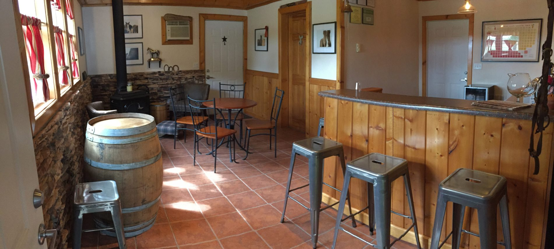 Tasting room at Crooked Creek Winery, wooden bar with metal top and metal stools. tile floor.