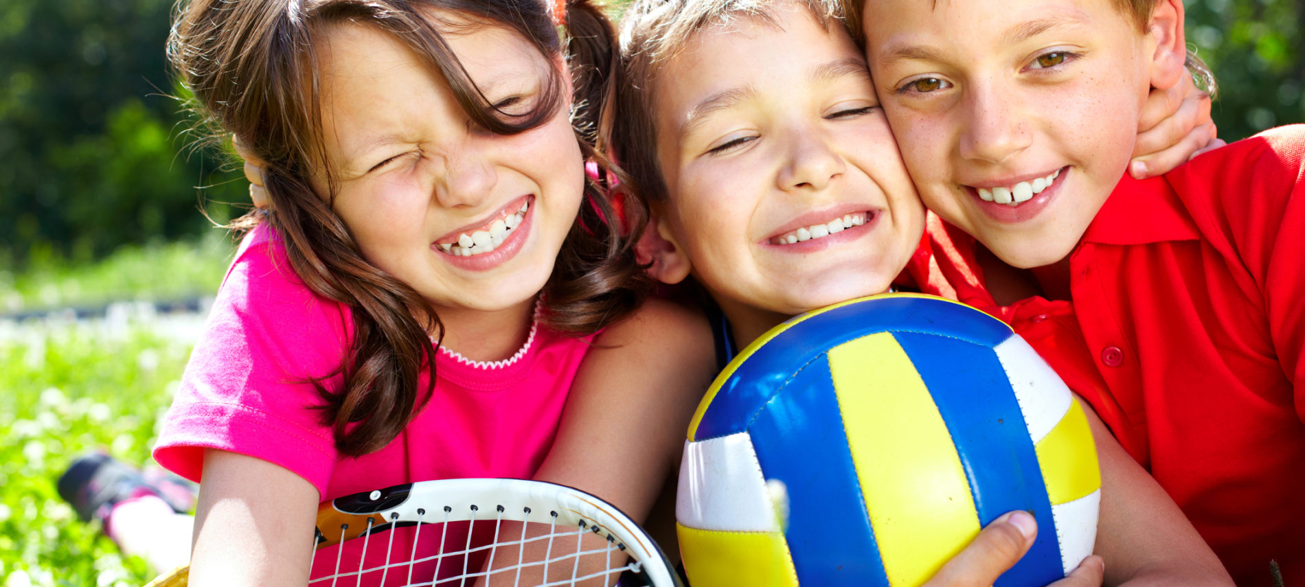 Three happy kids playing on grass, soccer ball and racket..