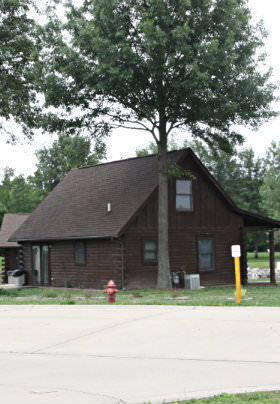 Brown cabin with 2 stories and porch surrounded by trees, red fire hydrant and street sign.