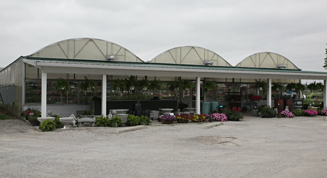 Large three domed greenhouse with various concrete statues and bird baths, hanging plants at entrance.