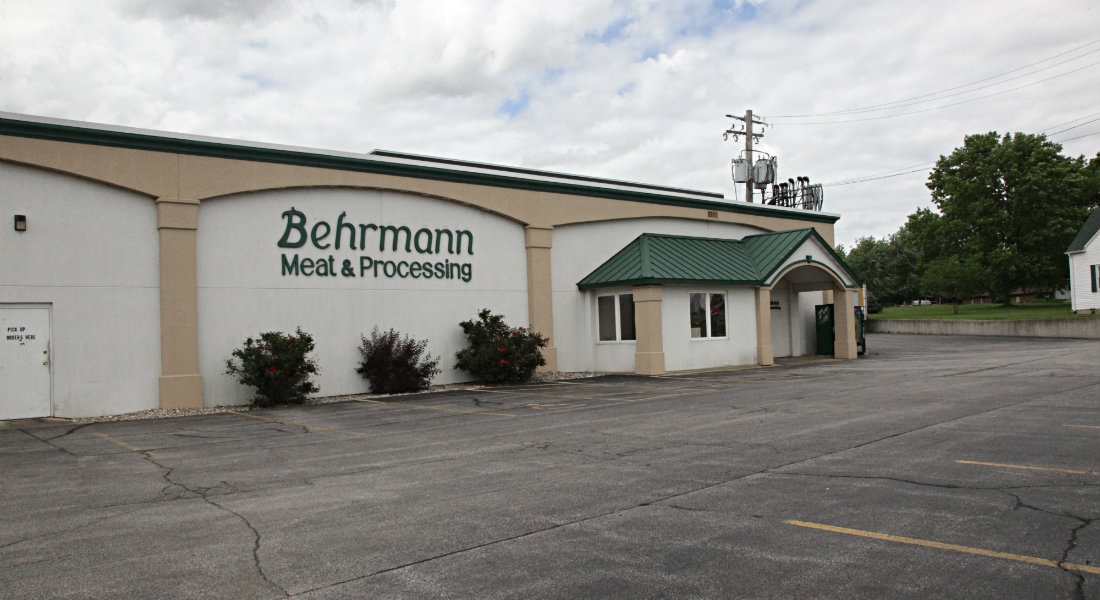 Tan and cream building with green room, Behrmann Meat and Processing Sign, three bushes with berries.