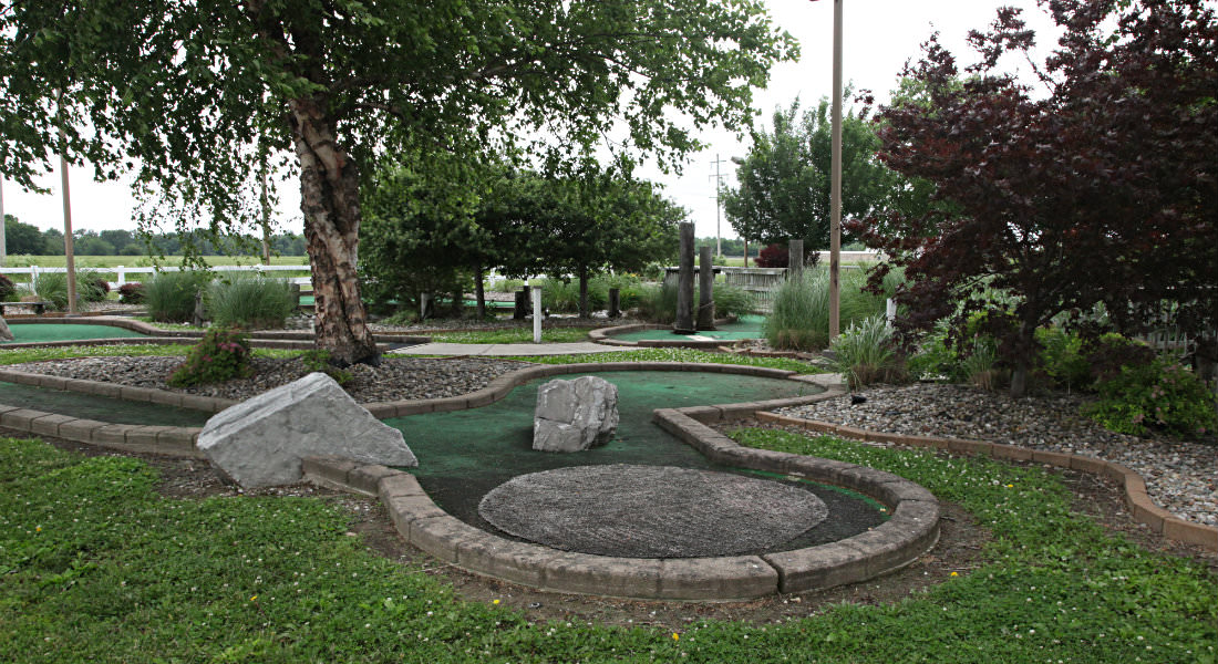 Miniature golf course putting greens with trees and grass surounding.