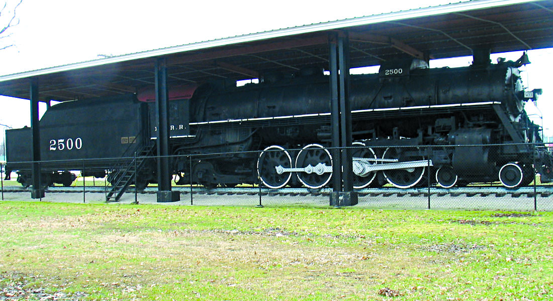 Black train cars sitting under covered depot with stairs to get into cars and number 2500 on side.