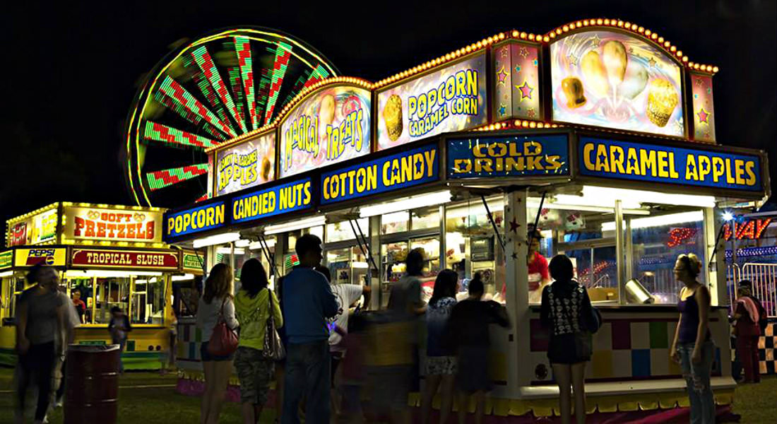 Patrons walking around and gathering around lit concession and carnival rides at night.