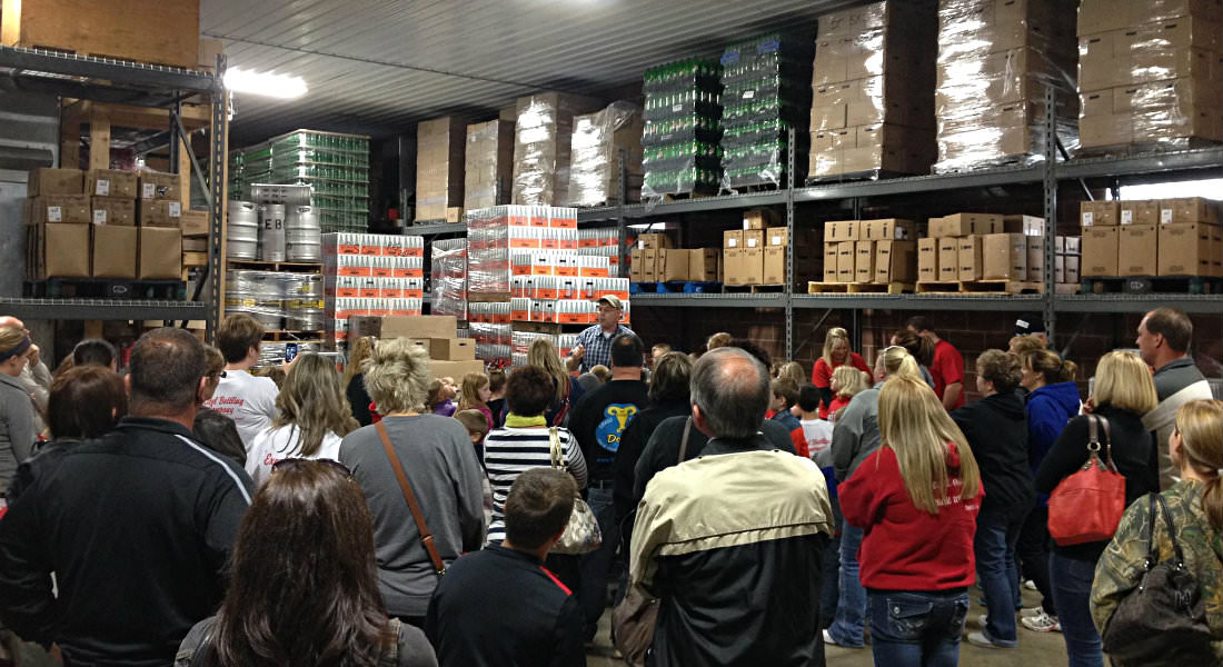 Group of people of varying ages congregated in warehouse with silver metal racks full of boxes.