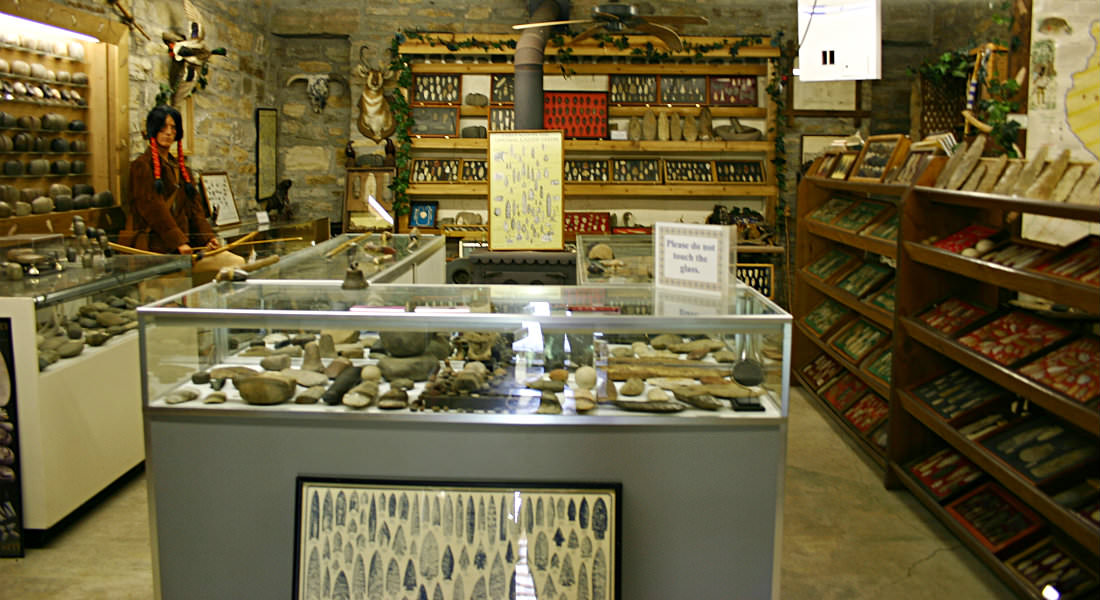 Room with glass display cases and shelving on both sides with Indian artifacts, Indian Statue with braids.