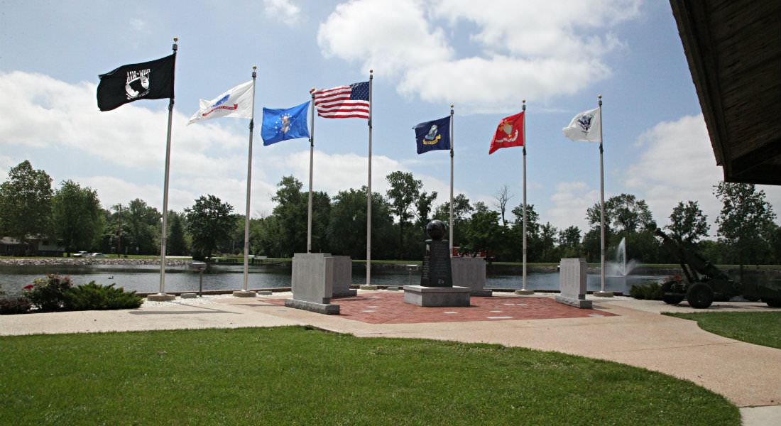 Cement Memorial Walls with engraved names by stream, Amerian Flag and 6 others on poles around memroial., water fountain.