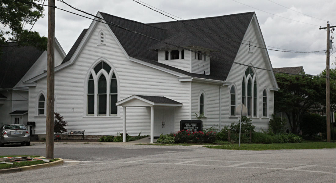 Large white sided church on corner with grey car on angled parking slot on street, sign with services information.