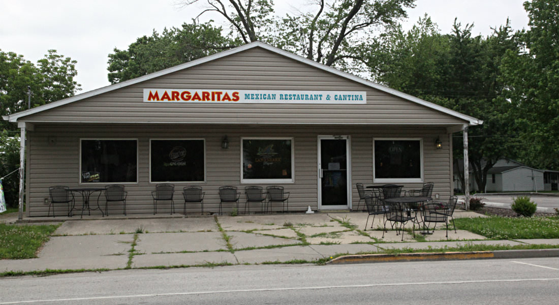 Tan sided building with covered porch with metal tables and chairs, sign for Margaritas Mexican Restaurant and Cantina.