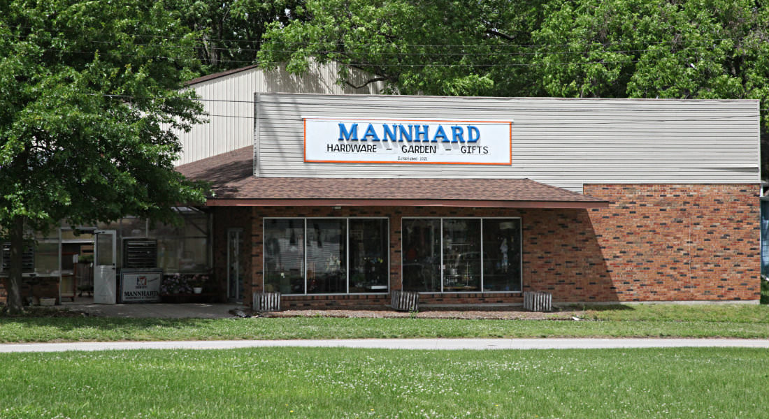 Red brick storefront with tan sided 2nd floor, white sign with blue letters Mannhard Hardware-Garden-Gifts.