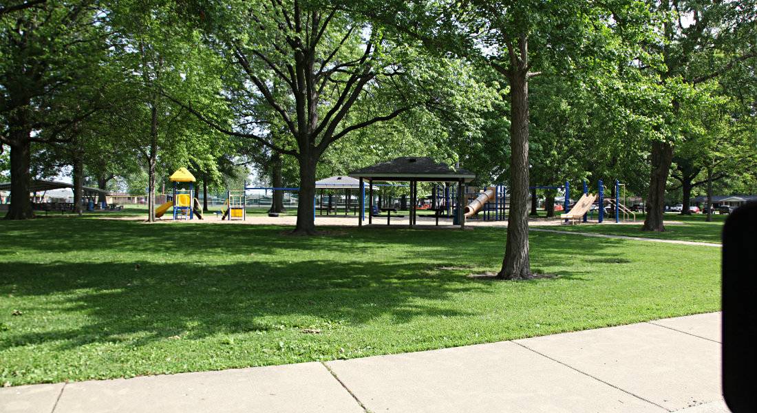 Park with covered shelters and playground equipment under trees, sidewalk surrounding grass.