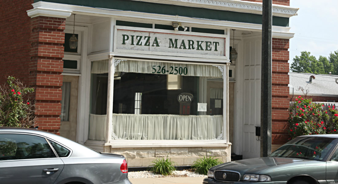 Red brick building with large picture window Pizza Market Sign with phone number, cars on street.