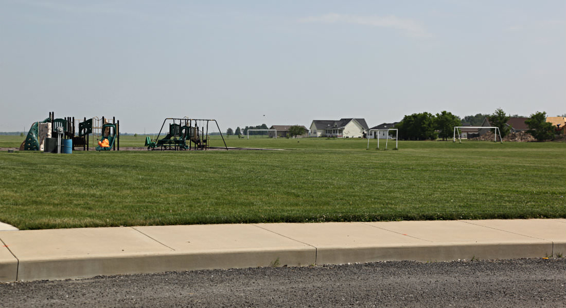 Open grassed area with variety of playground equipment, soccer nets, yellow house in distance.